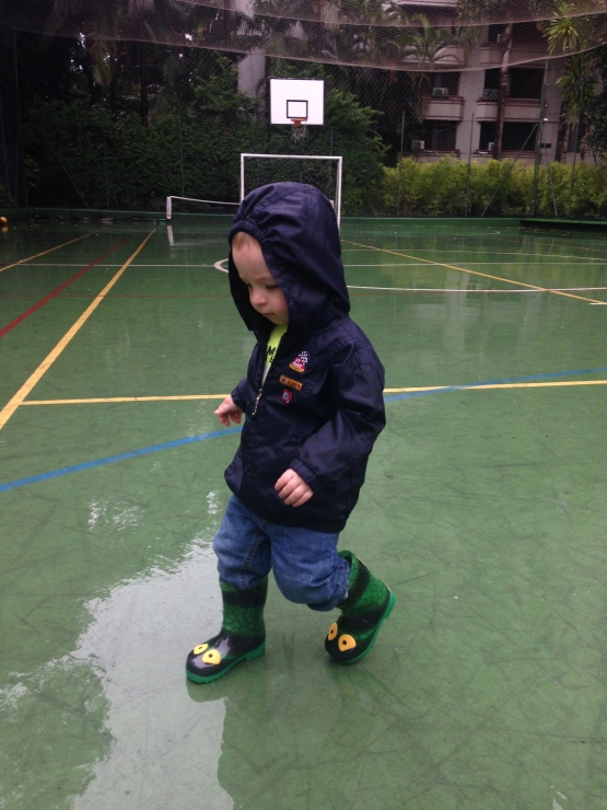 Splishing and splashing in the rain! Loving the boots from his godparents Mike & Mo!