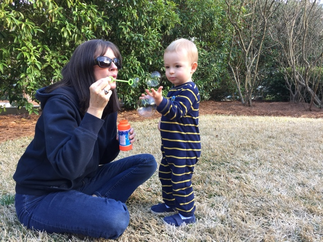 Blowing bubbles in the yard with Gigi.